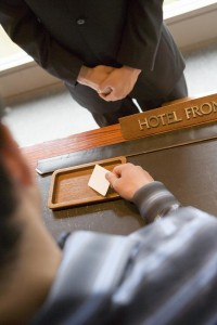 Young woman receiving key card from receptionist