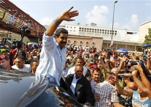 Acting Venezuelan President Maduro waves to supporters as he leaves after voting for the successor to the late President Chavez, in Caracas
