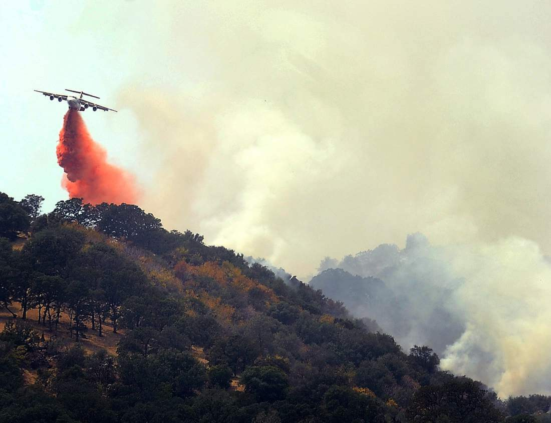 CalFire Air tanker drops fire retardant on a ridge above Pleasants Valley Rd. near Winters, Calif., as crews continue to battle the Wragg Fire on Thursday, July 23, 2015.  (Joel Rosenbaum/The Vacaville Reporter via AP)