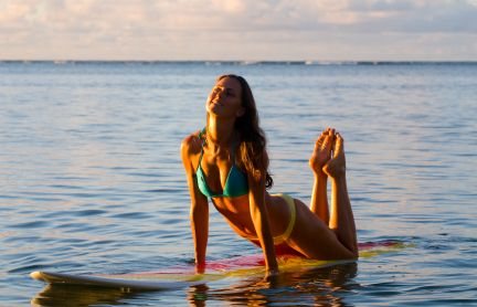 attractive woman in a bikini lying on a surfing board at sunset and smiling