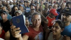 A Cuban migrant man receives his passport with the visa granted by the immigration office at the border post with Panama in Paso Canoas