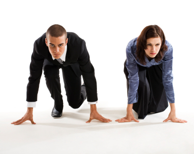 Young businesswoman and young businessman side-by-side in starting position and determined to win. Concepts: competition; corporate race; power struggle; battle of the sexes. Studio photography, isolated on white background.