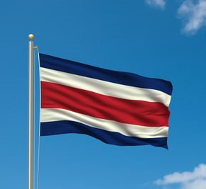 Flag of Costa Rica waving in the wind in front of blue sky