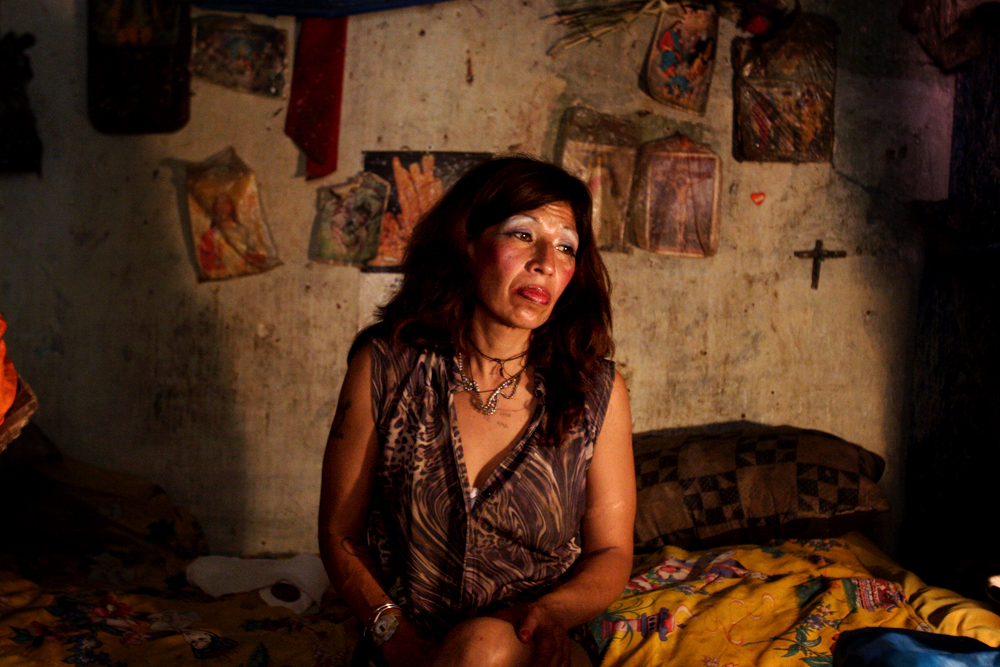 "A prostitute from El Salvador who identifies herself as Vilma poses for a portrait as she waits for clients in her rented room on a street called in Spanish ""La Linea,"" or ""The Strip,"" where dozens of women work as prostitutes in Guatemala City, Monday, April 23, 2007. (AP Photo/Alexandre Meneghini)"