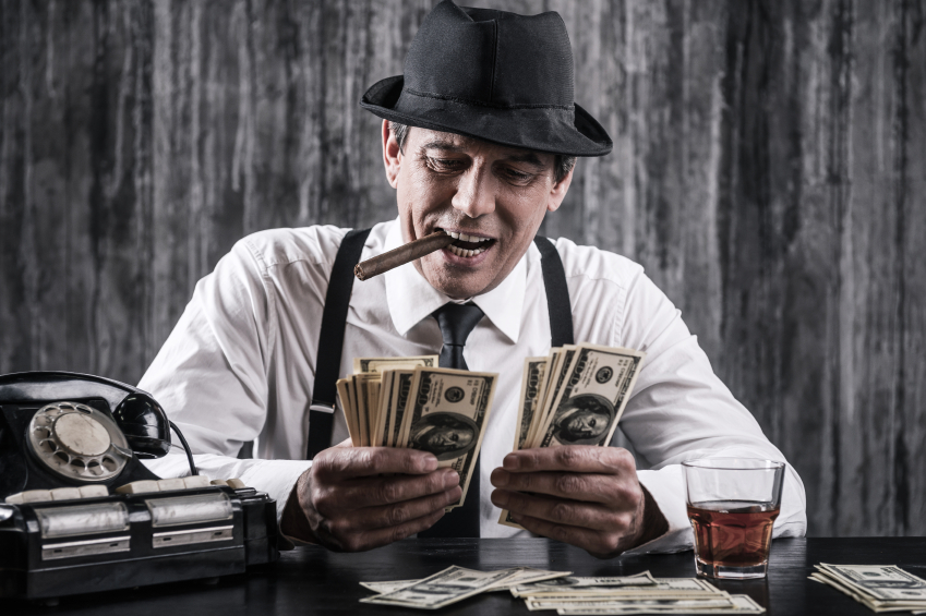 Money and power. Senior gangster in shirt and suspenders counting money and smiling while sitting at the table