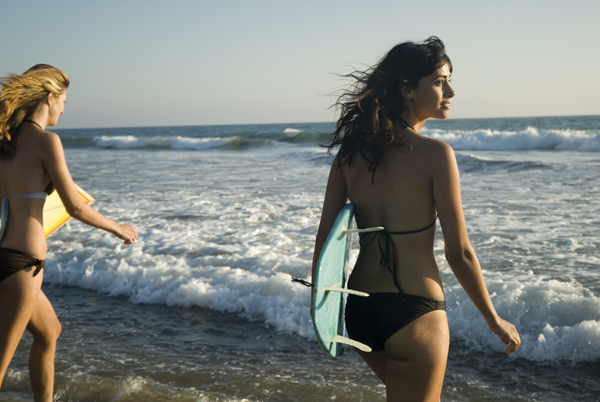 Two young female surfer girls walk out to the surf, Zuma California USA.