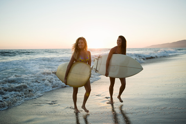 Female surfers by the sea at sunset