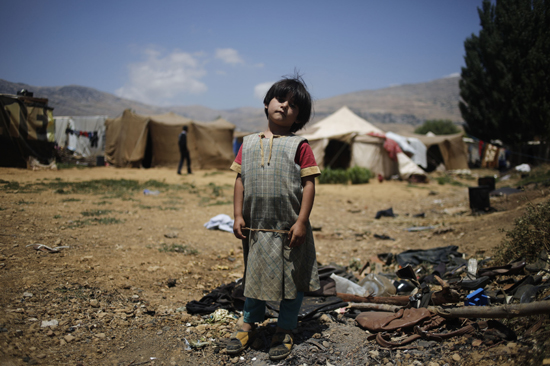 Raghed, 7, stands among rubbish at an informal refugee settlement in Qab Elias in Lebanon's Bekaa Valley. This camp is home to families who fled to Lebanon hundreds of kilometers from their home in Hassakah near to Syria's northern border. Many told CRS their homes had bee after their home was destroyed in an airstrike. Fighting between Kurdish groups and Turkish troops prevented a safe passage to nearby Turkey. There is no electricity at the camp and water has to be drawn by hand from a well. Families here have received critical food, shelter support and living supplies from Catholic Relief Services and our partner, Caritas Lebanon. CRS, Caritas and other local partners are helping more than 15,000 refugees across the country, and more than 100,000 Syrians across the region. An estimated 100,000 people have been killed within Syria, with millions uprooted inside the country and at least 1.2 million people having fled into neighboring countries to seek help.
