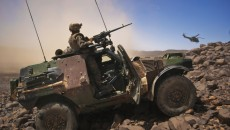 A French soldier stands guard in an armoured vehicle as a helicopter carrying Army Chief of Staff General Bertrand Ract-Madoux leaves a position in the Terz valley, about 60 km (37 miles) south of the town of Tessalit in northern Mali March 21, 2013. France has deployed some 4,000 troops to Mali, alongside a regional African force, in a nine-week operation that has driven Islamists into desert hideaways and mountains near the Algerian border. Picture taken March 21. REUTERS/Francois Rihouay (MALI - Tags: POLITICS CIVIL UNREST CONFLICT TPX IMAGES OF THE DAY) - RTXXWGB